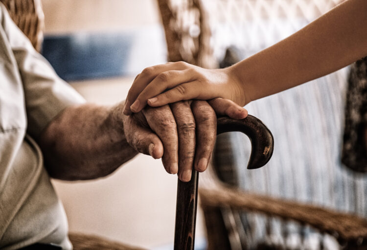 child's hand over old man's hand holding a cane.